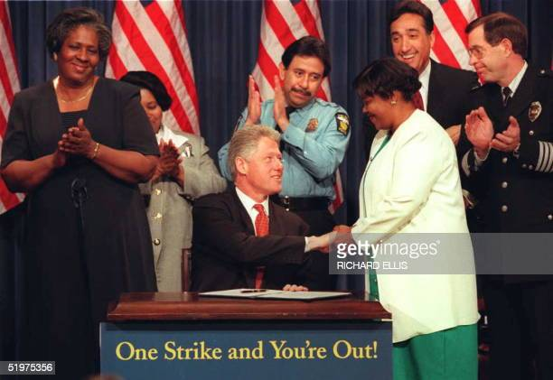 President Bill Clinton shakes hands with public housing resident Deborah Shaw after signing an executive order targeting crime in public housing and...