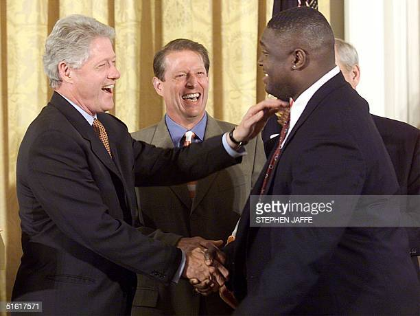 President Bill Clinton shakes hands with Tennessee's defensive tackle Billy Earl Ratliff as Vice President Al Gore looks on prior to honoring the...