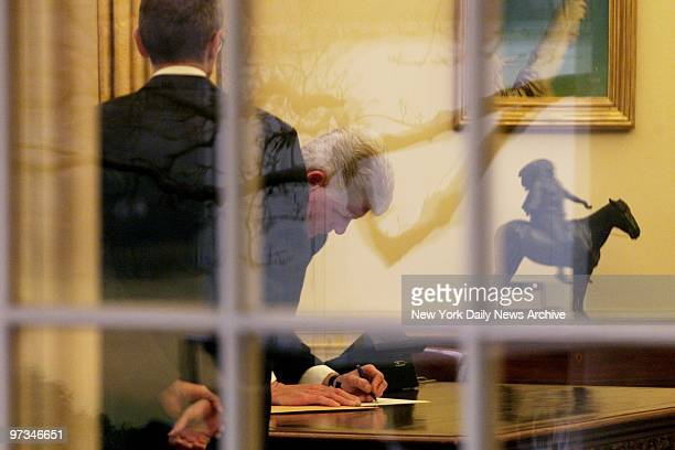 President Bill Clinton signs papers for the last time in the Oval Office before departing With him is Chief of Staff John Podesta