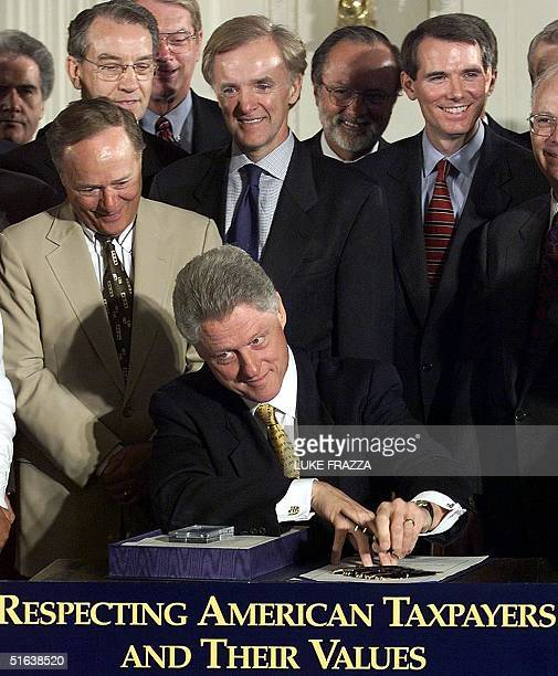 President Bill Clinton signs the IRS Restructuring and Reform Act of 1998 before members of the US Congress 22 July at the White House in Washington...