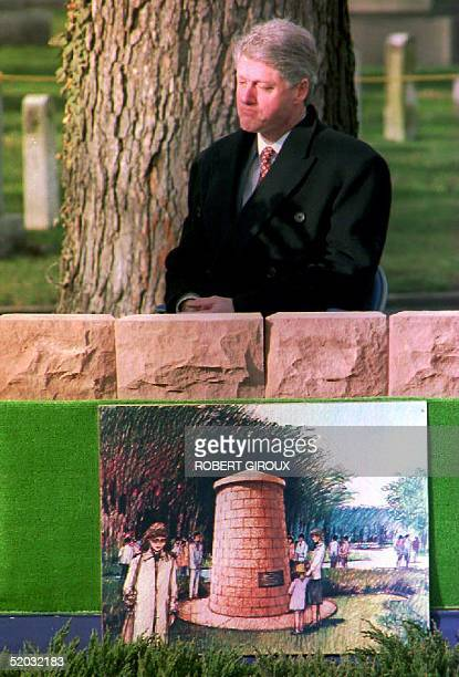 S President Bill Clinton sits behind an artists' rendition of a trditional Scottish burial marker known as a cairn during ground breaking ceremonies...