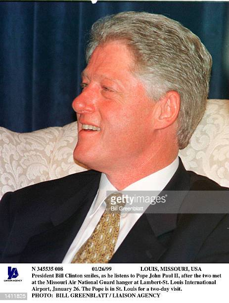 President Bill Clinton smiles as he listens to Pope John Paul II after the two met at the Missouri Air National Guard hanger at LambertSt Louis...