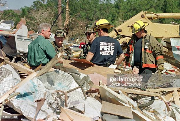 President Bill Clinton speaks 25 February to members of the Osceola Fire Department and military personel as they go through the debris left by a...