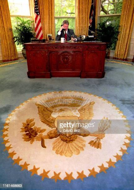 US President Bill Clinton speaks to community leaders via a conference telephone call from the Oval Office at the White House 04 May