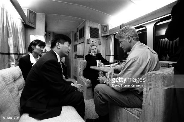 President Bill Clinton speaks with governor of Washington Gary Lock and his wife Mona Lee on the campaign bus while First Lady Hillary Clinton looks...