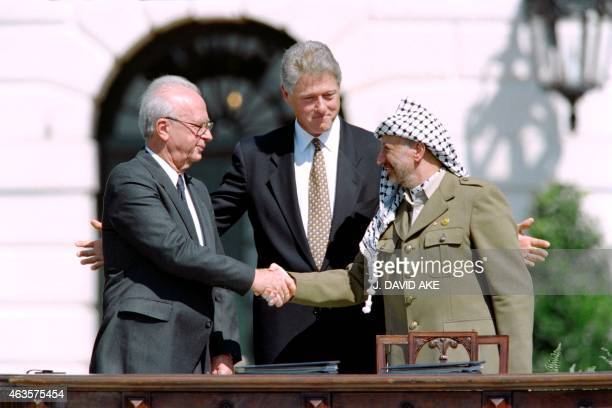 President Bill Clinton stands between PLO leader Yasser Arafat and Israeli Prime Minister Yitzahk Rabin as they shake hands for the first time, on...