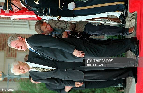 President Bill Clinton stands with Russian President Boris Yeltsin 20 June at Phipps House in Denver CO as they arrive for the first working dinner...