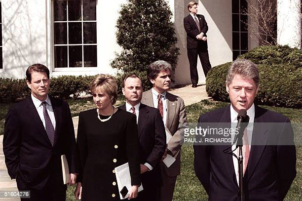 President Bill Clinton stops to speak to reporters 24 March 1994 as Vice President Al Gore Chief of Staff Mack McClarty and White House spokeswoman...