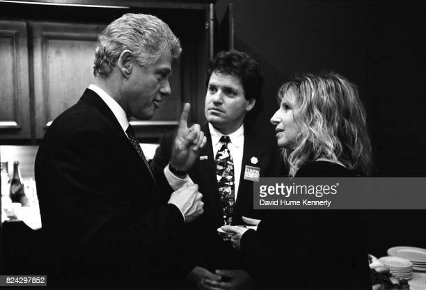President Bill Clinton talks with singersongwriter Barbra Streisand and his halfbrother Roger Clinton on election night backstage at the Old State...