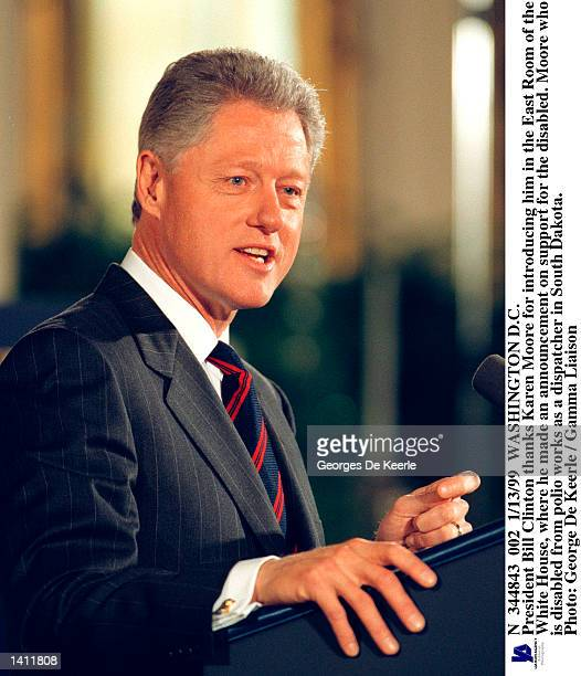 President Bill Clinton thanks Karen Moore for introducing him in the East Room of the White House January 13, 1999 where he made an announcement on...