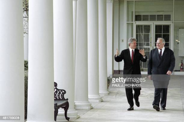 US President Bill Clinton walks with German Chancellor Helmut Kohl through the collonade adjacent to the Rose Garden at the White House on March 26...