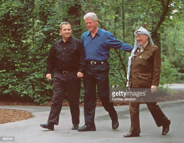 President Bill Clinton walks with Israeli Prime Minister Ehud Barak and Palestinian President Yasser Arafat July 11, 2000 at Camp David during peace...