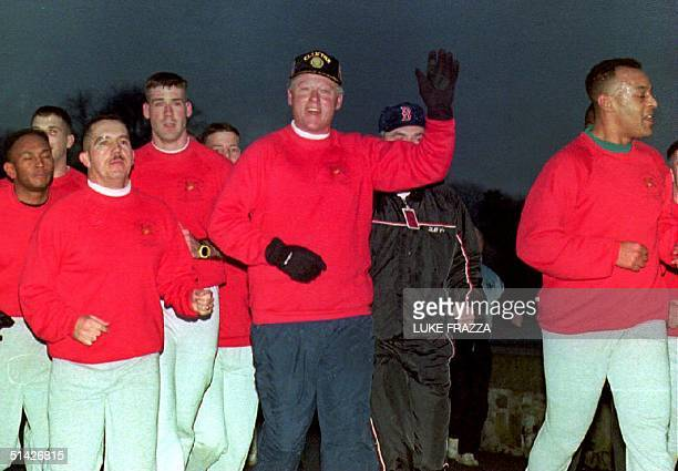 S President Bill Clinton waves during an early morning jog in Geneva Switzerland 16 January 1994 with Marines from the US Embassy before his meeting...