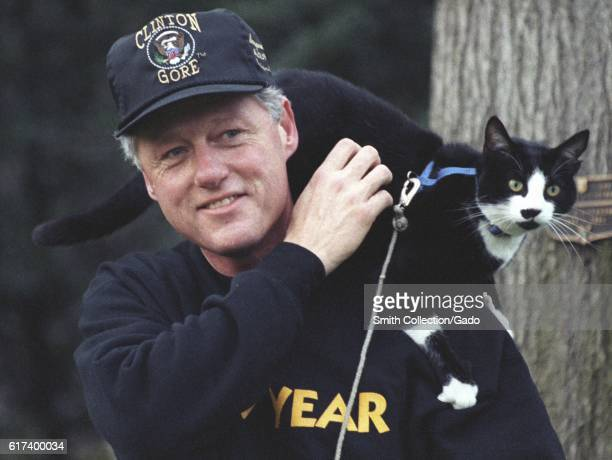 President Bill Clinton, wearing pullover sweatshirt and a Clinton-Gore administration baseball hat, smiles while taking a walk on the White House...