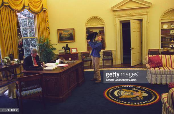 President Bill Clinton wearing suit and glasses works at his desk in the Oval Office while the First Daughter Chelsea Clinton wearing khaki trousers...
