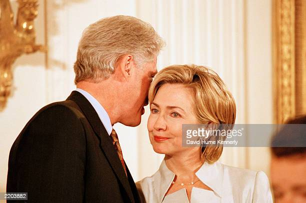 President Bill Clinton whispers in wife Hillary's ear during the Medal of Freedom event where former President Gerald R. Ford was honored at the...