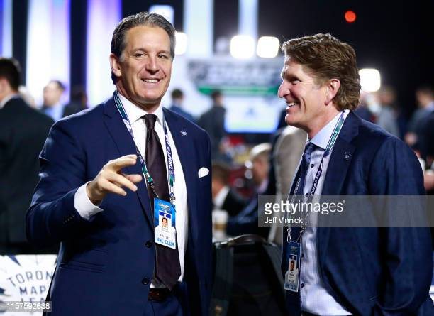 President Brendan Shanahan and head coach Mike Babcock of the Toronto Maple Leafs talk on the draft floor during Rounds 27 of the 2019 NHL Draft at...