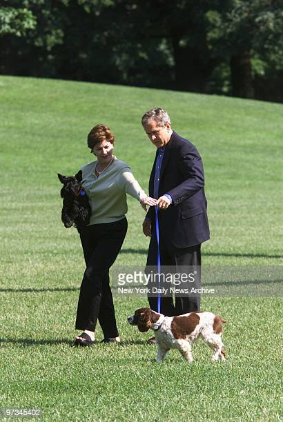 President Bush and wife Laura arrive back at the White House after a trip to Camp David in Maryland The president holds the leash of their English...