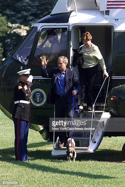 President Bush and wife Laura disembark from helicopter upon return to the White House after a trip to Camp David in Maryland The president holds the...