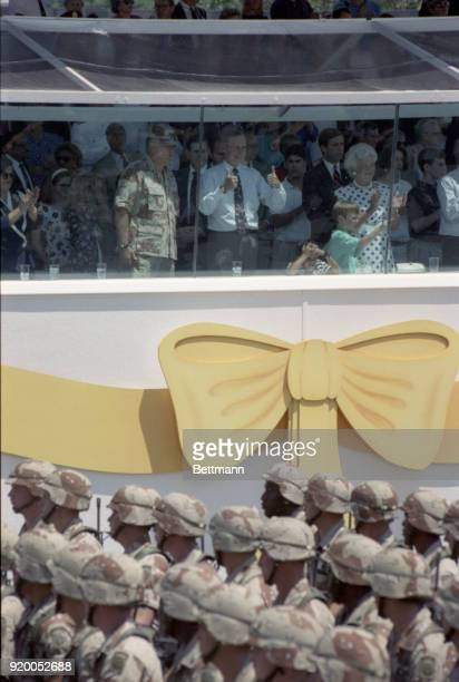 President Bush gives a thumbs up sign as troops pass the reviewing stand during the victory parade celebrating the allied victory in the Persian...