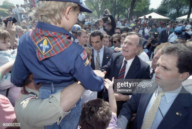 President Bush greets a cub scout during a brief stop by the mall to view military demonstrations set up a part of the desert storm victory...