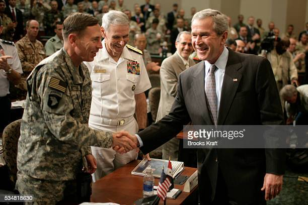 President Bush shakes hands with Gen David H Petraeus commander of multinational forces in Iraq as Adm William J Falloncommander of US Central...