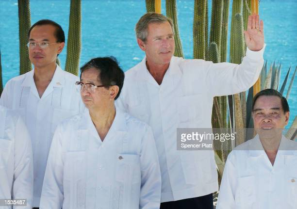 President Bush waves while standing with Vietnamese Prime Minister Phan Van Khai Taiwan envoy Lee Yuan Tseh and Singapore Trade Minister George Yong...