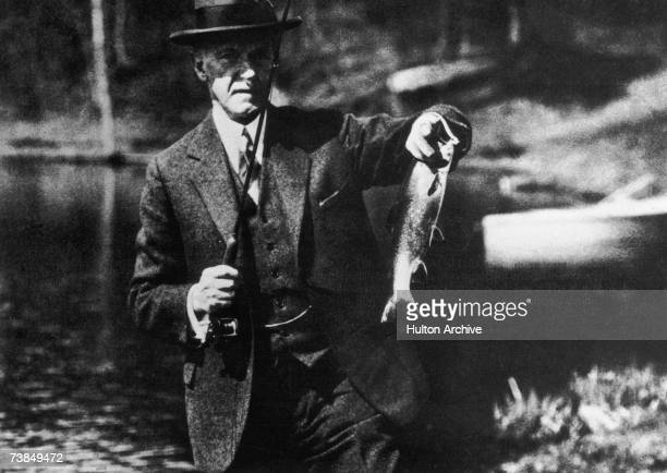 US President Calvin Coolidge displays a catch during a fishing expedition circa 1925
