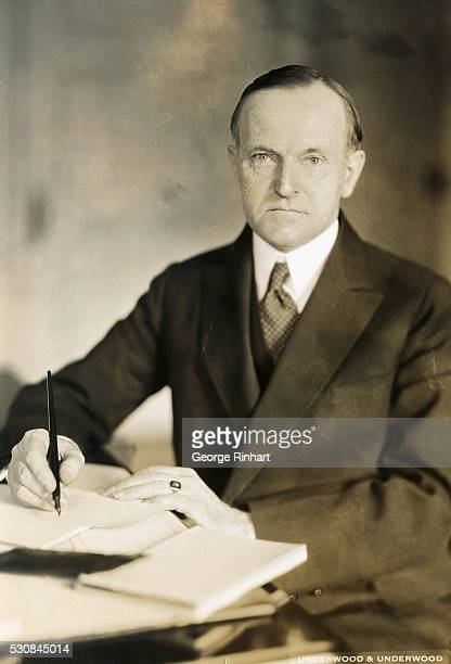 President Calvin Coolidge is shown seated and writing at a desk