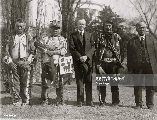 President Calvin Coolidge posed fulllength portrait standing facing front with four Osage Indians White House in the background 1925