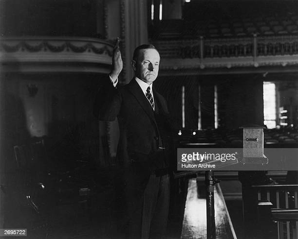US president Calvin Coolidge raises his right hand while standing at a podium for his swearingin ceremony Washington DC He served two terms