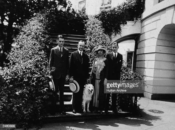 President Calvin Coolidge stands outdoors with his wife Grace their two sons and their pet white collie 'Rob Roy ' 1920s