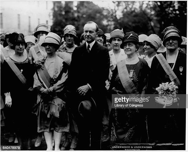 President Calvin Coolidge stands with members of a group called the Daughters of 1812