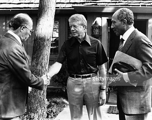 President Carter shakes hands with Israeli Prime Minister Menachem Begin while Egyptian President Anwar Sadat stands nearby The three leaders are...