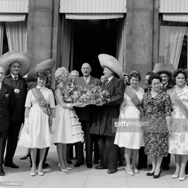"""President Charles de Gaulle and his wife Yvonne de Gaulle pose alongside the """"Queen of Halles"""" accompanied by """"Forts des Halles"""" who came to offer..."""