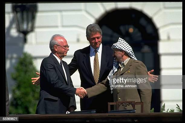 President Clinton smiling as PLO chairman Yasser Arafat & Israeli PM Itzak Rabin seal signing of Israel-PLO peace accord with historic handshake, at...