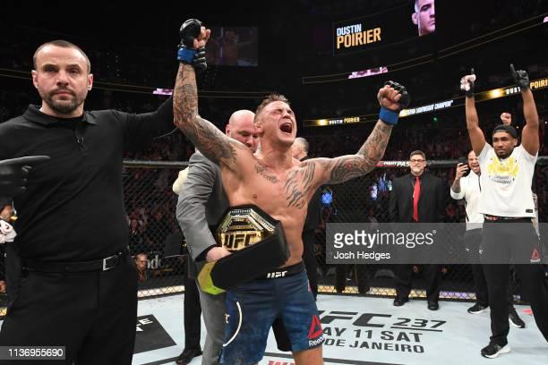 UFC President Dana White places the interim lightweight championship belt on Dustin Poirier after defeating Max Holloway in their interim lightweight...