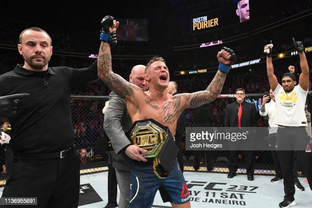 President Dana White places the interim lightweight championship belt on Dustin Poirier after defeating Max Holloway in their interim lightweight...