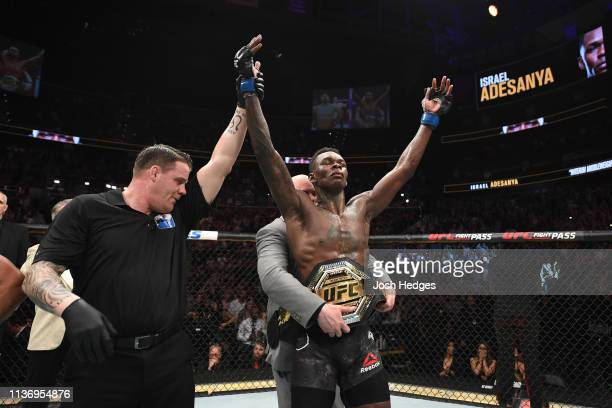 UFC President Dana White places the interim middleweight championship belt on Israel Adesanya after defeating Kelvin Gastelum by unanimous decision...