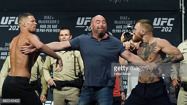 President Dana White separates mixed martial artist Nate Diaz and UFC featherweight champion Conor McGregor as they face off during their weigh-in...