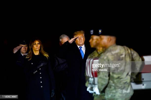 S President Donald J Trump and first lady Melania Trump salute as military personnel carry a transfer case for fallen service member US Army Chief...