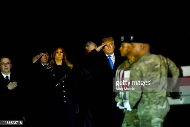 S President Donald J Trump first lady Melania Trump and US Deputy Secretary of Defense David Norquist salute as military personnel carry a transfer...