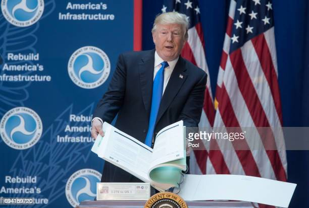 President Donald J Trump flips through environmental impact statements for a road while delivering remarks on infrastructure investment and...