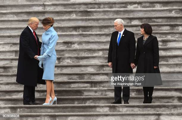 President Donald J Trump holds hands with First lady Melania Trump as they take their places beside Vice President Pence and Karen Pence while they...
