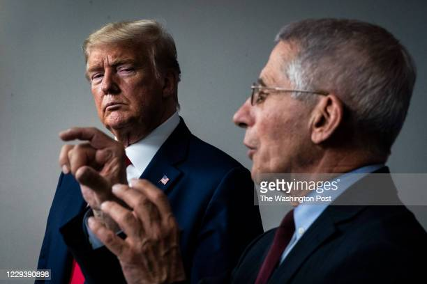 President Donald J. Trump listens as National Institute for Allergy and Infectious Diseases Director Dr. Anthony Fauci speaks with members of the...