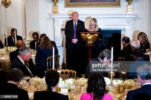 President Donald J Trump listens as Pastor Paula White leads a prayer at a dinner celebrating Evangelical leadership in the State Dining Room of the...