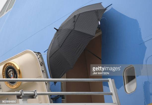 US President Donald J Trump opens un umbrella before stepping off of Airforce One after arriving in Nashville Tennessee on January 8 2018 / AFP PHOTO...