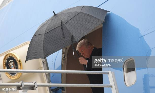 US President Donald J Trump opens un umbrella before stepping off of Airforce One after arriving in Nashville Tennessee on January 8 2018