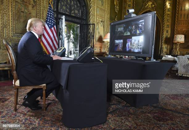 President Donald J Trump participates in a video teleconference call with military members on Christmas Eve in Palm Beach Florida on December 24 2017...