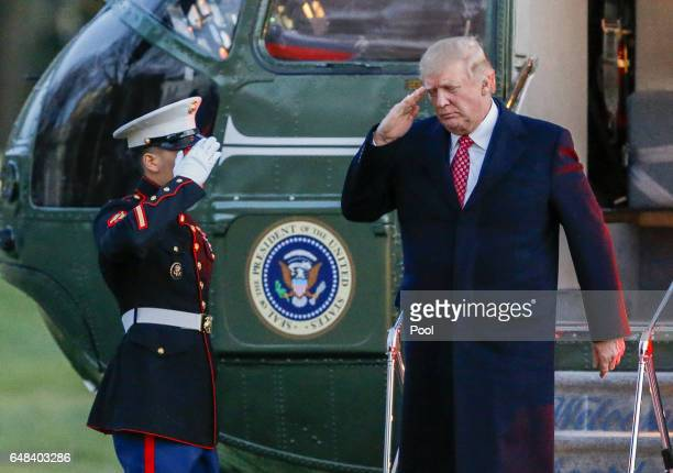 President Donald J Trump salutes as he disembarks Marine One on the South Lawn of the White House on March 5 2017 in Washington DC Trump is returning...